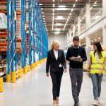 three professionals walking through a warehouse with their inventory management technology