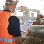 Construction worker using a tablet to access construction software on-the-go