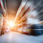 Warehouse industrial and logistics companies. Long shelves with a variety of boxes and containers. Toning the image. Motion blur effect. Bright sunlight.