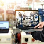 Man working in a manufacturing factory using a manufacturing ERP solution to streamline operations