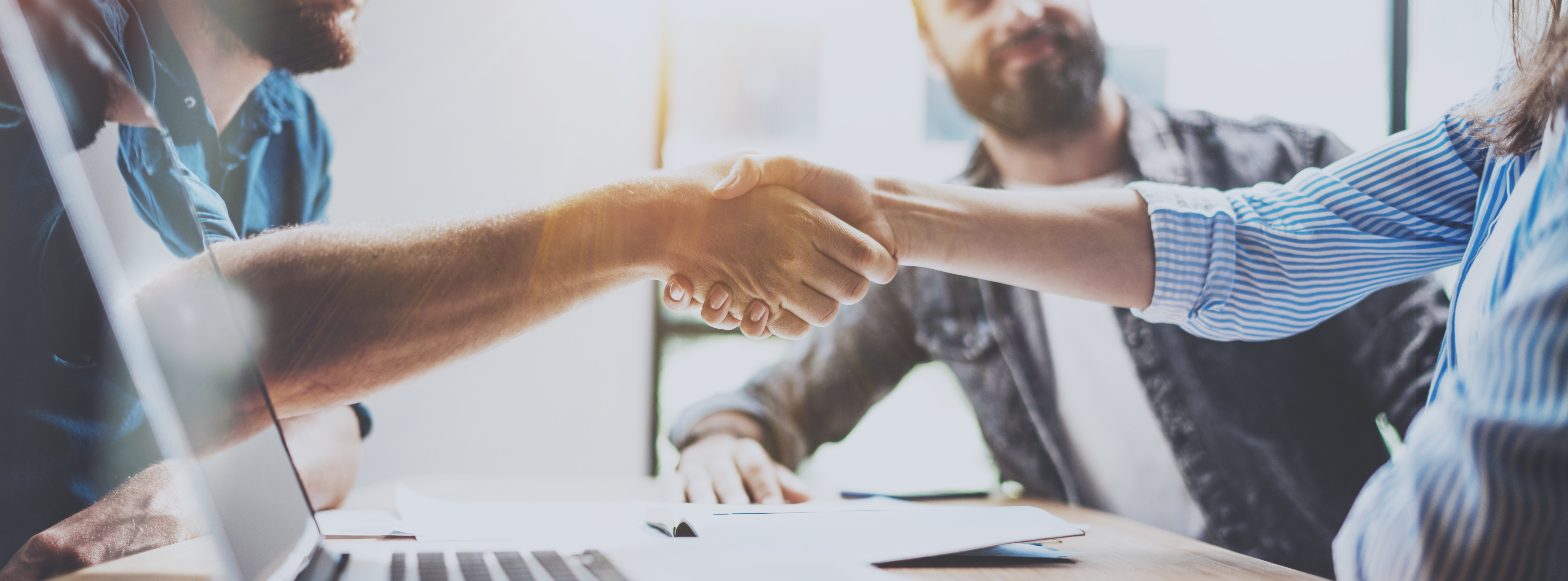 two coworkers handshaking after a successful deal after great meeting