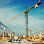 construction site with a large crane and clear blue sky