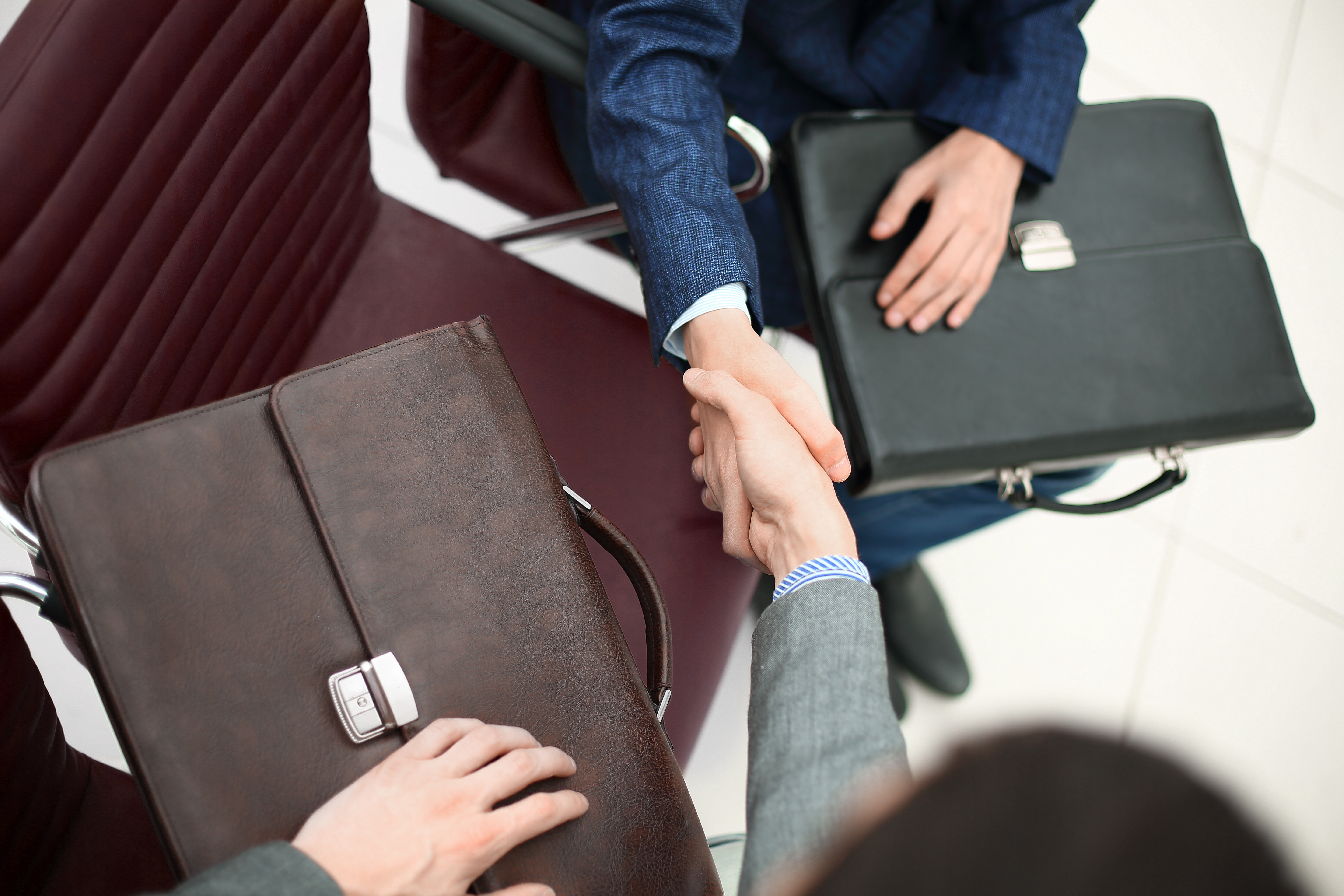 close up handshake of two business in the office lobby.
